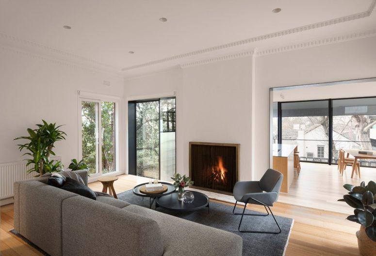 The living room is done with contemporary furniture, a built-in fireplace and potted plants
