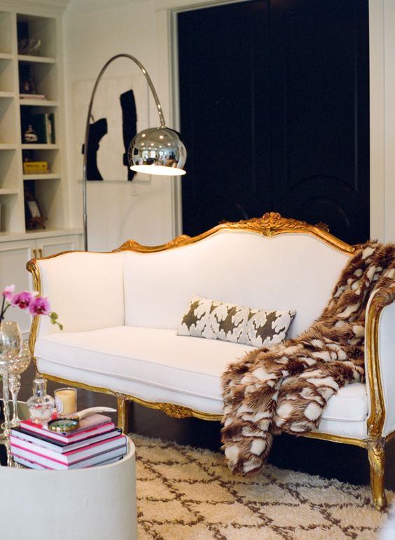 a contrasting contemporary space finished off with a beautiful vintage white sofa with gilded framing