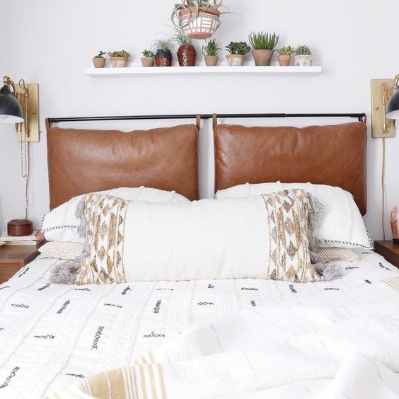 a neutral bed with embroidered and tasseled bedding and brown leather pillows as a headboard
