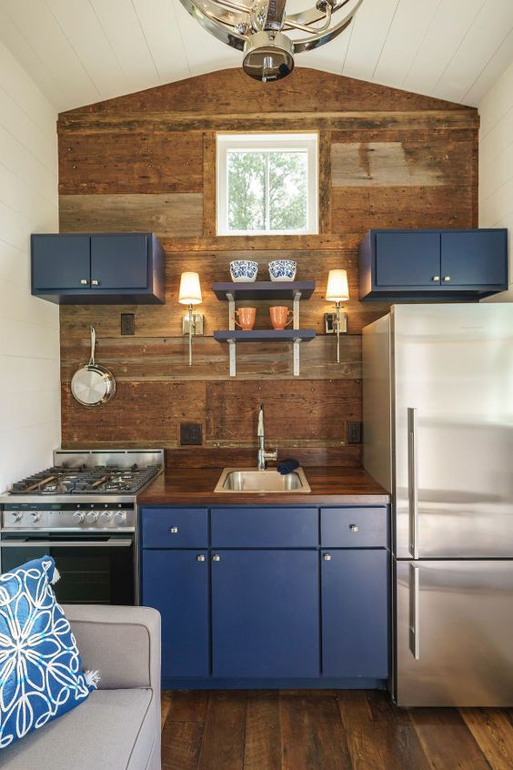 a tiny kitchen with a wooden statement wall, blueberry blue cabinets for a touch of color
