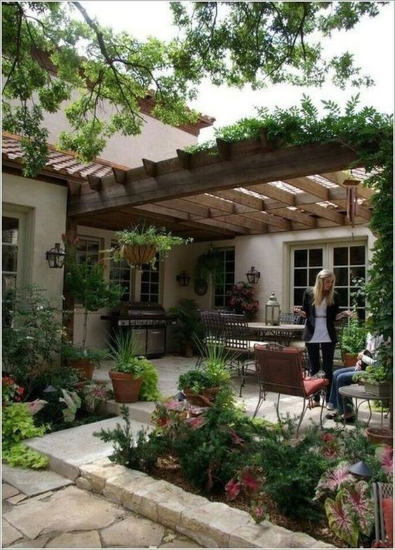 an outdoor living room with elegant furniture, potted greenery and blooms and a mini kitchen
