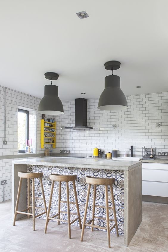 an ultra-modern kitchen done with white subway tiles, a concrete kitchen island with a seating space for dining here