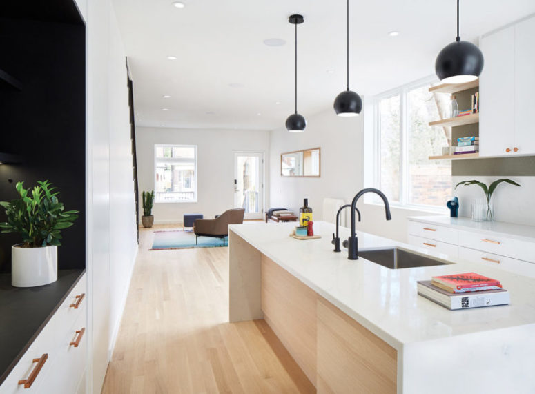 Black pendant lamps and faucets echo with the niche creating a bold look