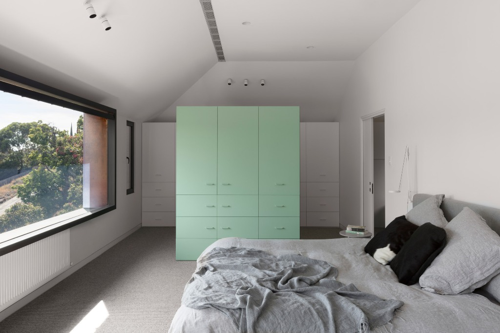 The bedroom features white and mint cabinets, a comfy bed and a view through a large window