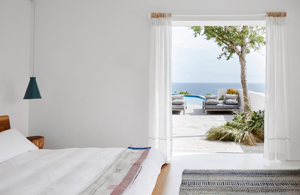 The bedroom is white, there's simple yet chic woodne furniture, blue lamps and an entrance to the terrace