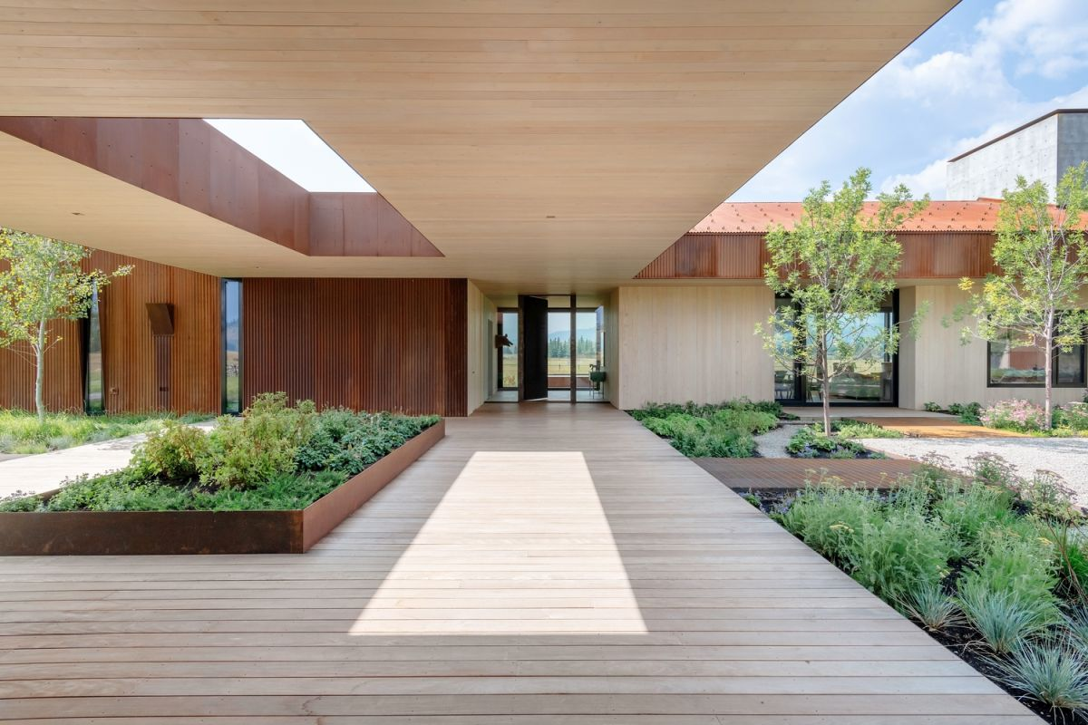 The house features large openings under the roof to fill the spaces with greenery and connect indoors with outdoors