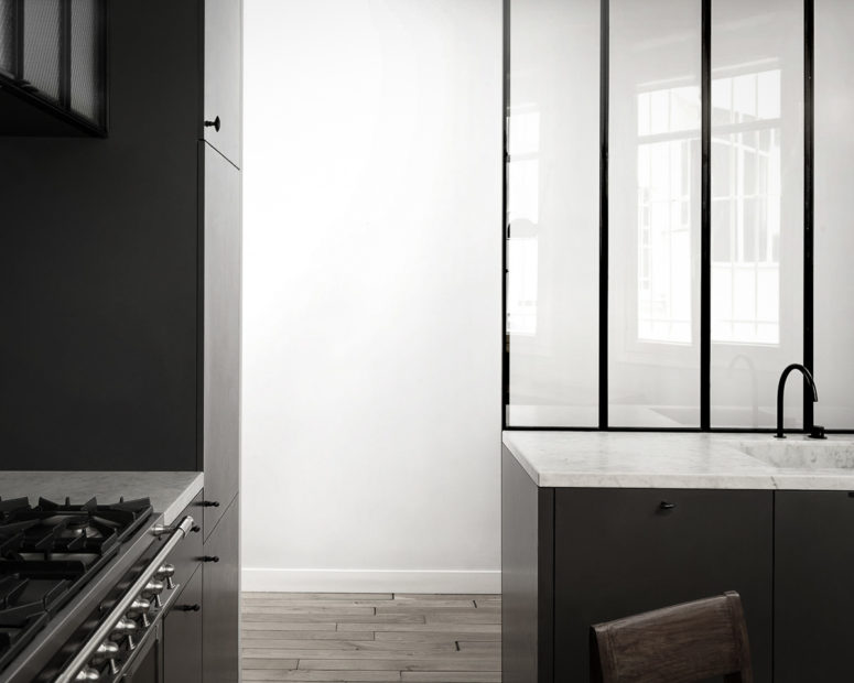 The kitchen is done with dark cabinets, white stone countertops and black frames plus frosted glass