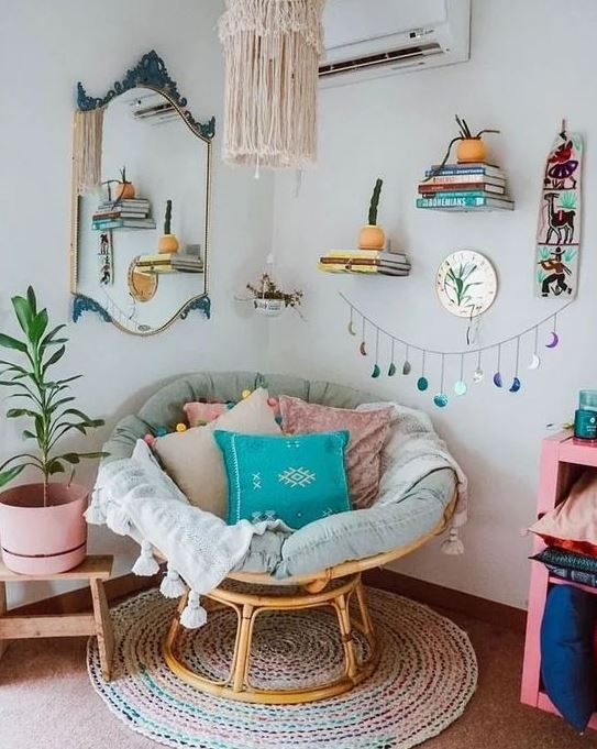 a colorful boho nook with a papasan chair with pastel pillows, a macrame chandelier and potted greenery and bright touches