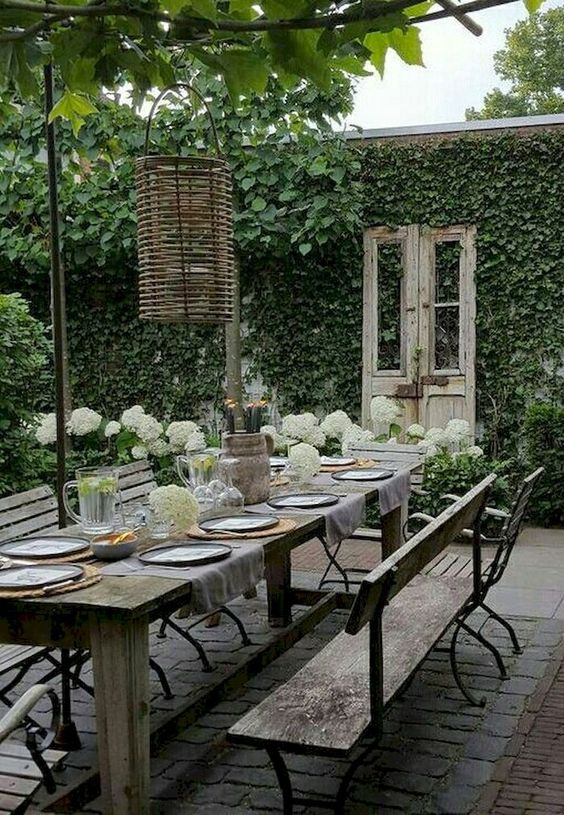 a garden dining space with vintage and shabby chic furniture, wicker lamps and living walls all around