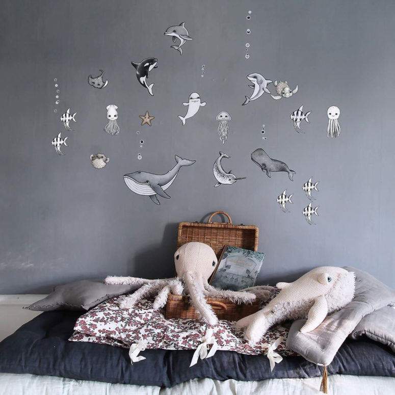 a grey nursery with a sea creature statement wall and some cute sea life plush toys