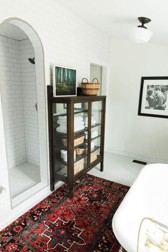 a modern bathroom with a bright rug, white tiles all over and a vintage dark stained glass armoire
