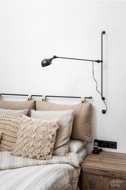 a neutral and peaceful bedroom with a textural bedding set, with hanging pillows as a headboard and a black sconce
