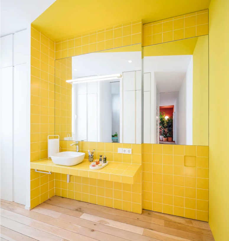 The color block bathroom is done with bright yellow tiles that also form a vanity and there are two large mirrors