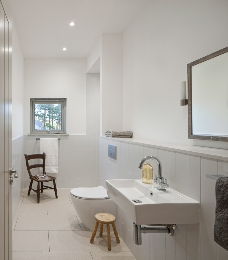 The bathroom is neutral, with white tules of various sizes and a window for more light