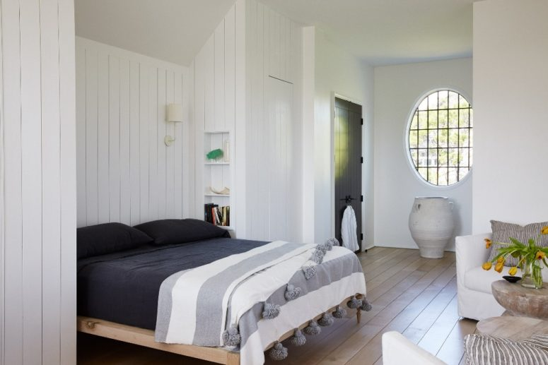 The bedroom is done with white walls, a bed in a niche and a creative round window
