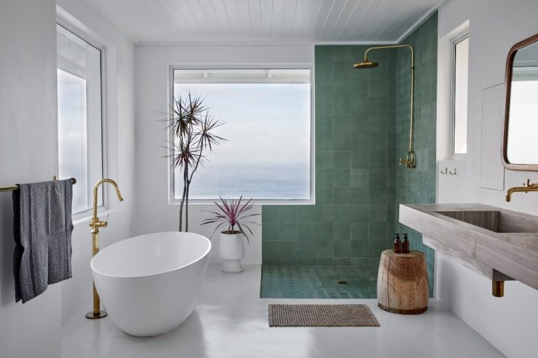 The master bathroom is done with an oval tub, a green tile shower space and a concrete sink