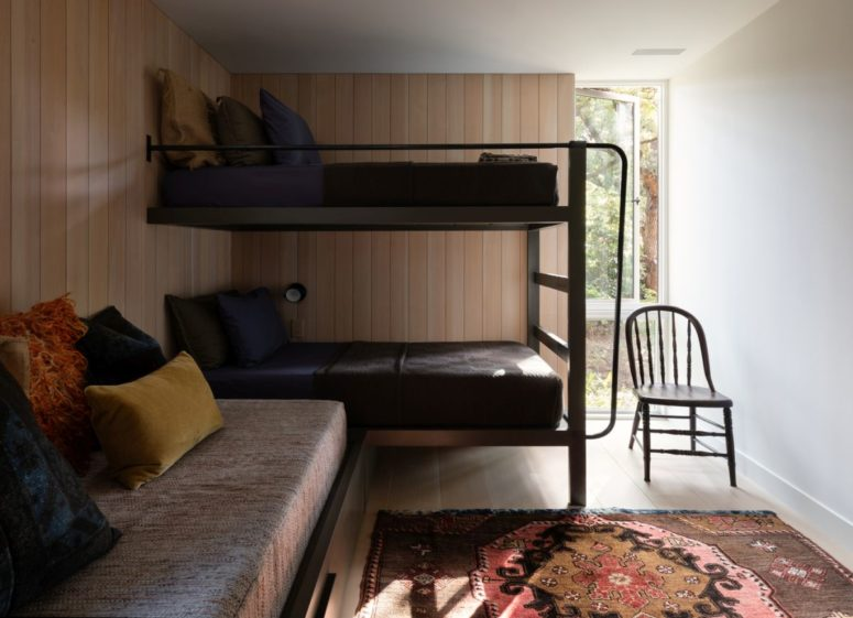 There's a guest bedroom with bunk beds and a sofa with pillows plus a bright rug