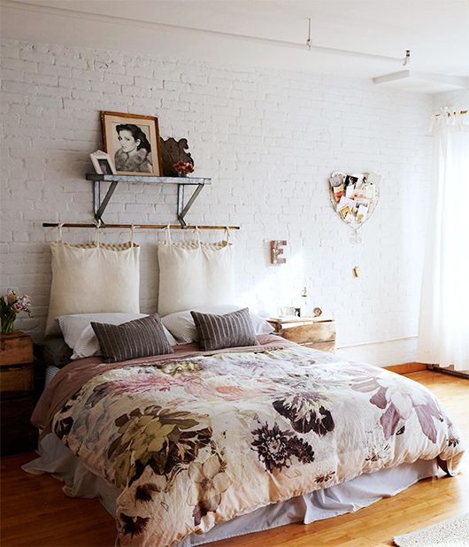 a bright and cheerful bedroom with floral bedding and hanging pillows for a headboard looks romantic and soft