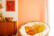 07 a bright space with a yellow papasan chair with a white futon and bright pillows plus a catchy floor lamp over it