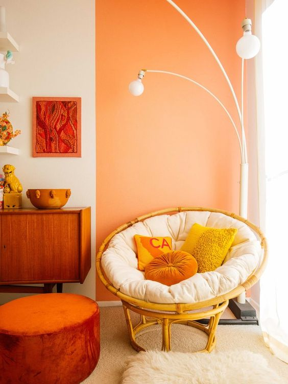 a bright space with a yellow papasan chair with a white futon and bright pillows plus a catchy floor lamp over it