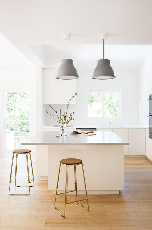a light-filled Scandinavian kitchen with a large kitchen island that features a longer countertop for comfortable eating here