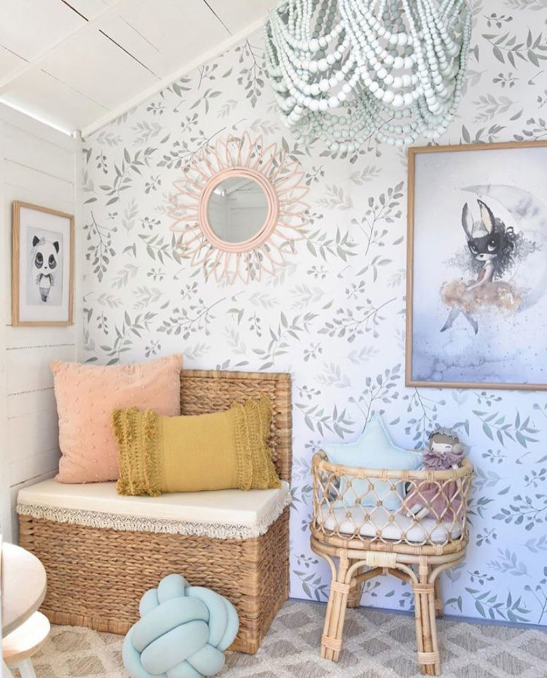 a sweet farmhouse nursery with a delicate leaf print wall that makes the space softer and more welcoming