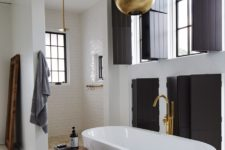 08 The bathroom features lots of blakc shutters, metallic lamps and a chic shower space