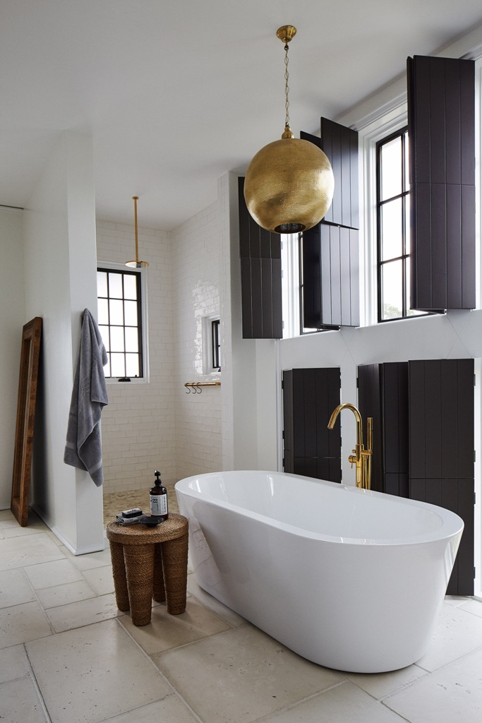 The bathroom features lots of blakc shutters, metallic lamps and a chic shower space