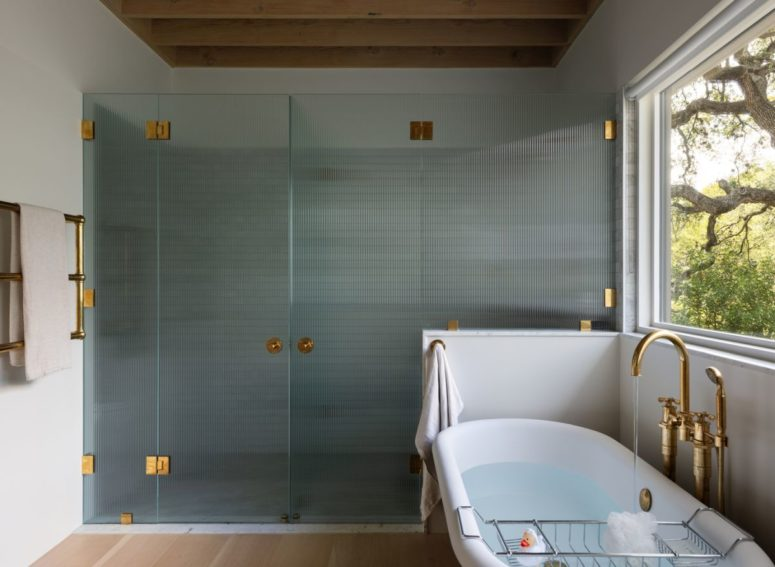 The bathroom has a shower area encased in textured glass with golden metal fixtures