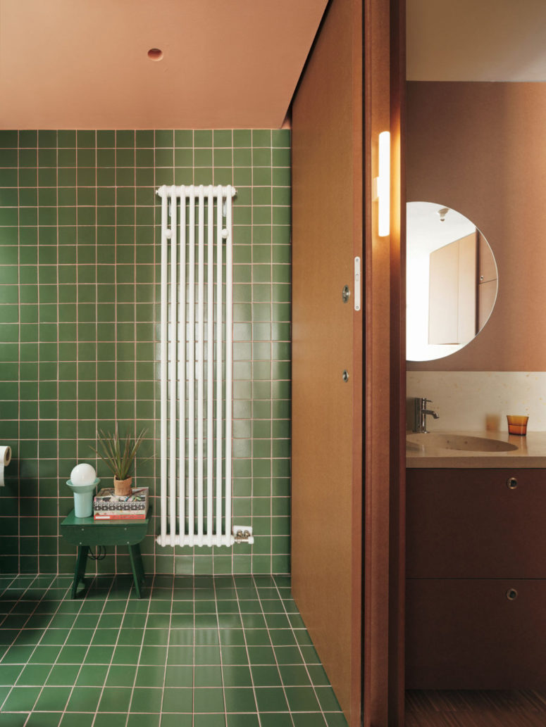 The bathroom is clad with green tiles and highlighted with pink grout for a touch of color