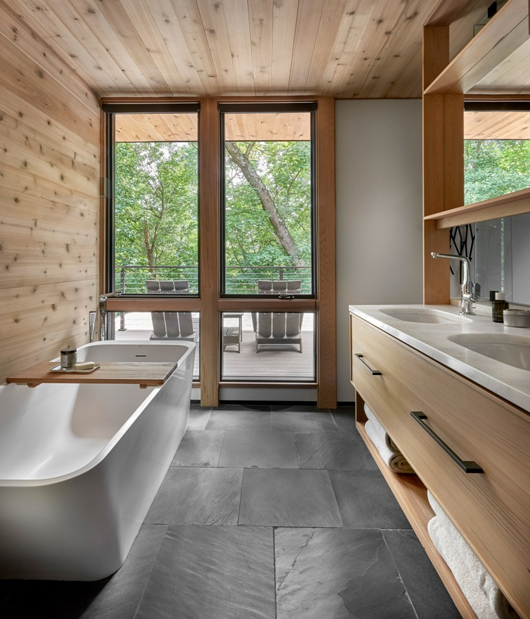The bathroom is done with dark tiles, lots of wood, a double vanity and a sculptural bathtub