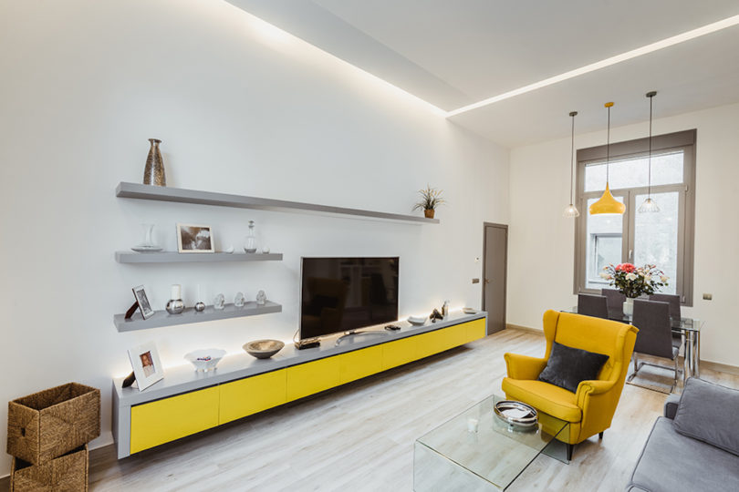 The contemporary living room is done with bright and neutral furniture, with a combo of yellow and grey
