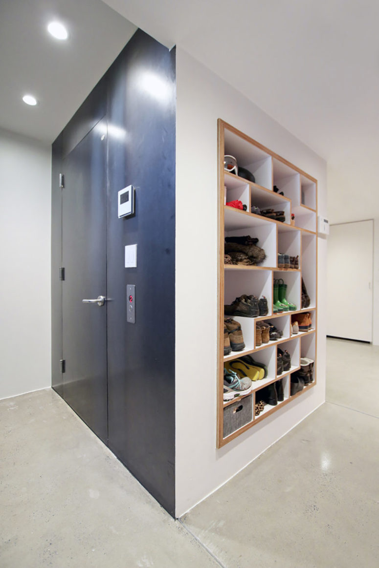 The mudroom features a creative shoe storage unit built into the wall