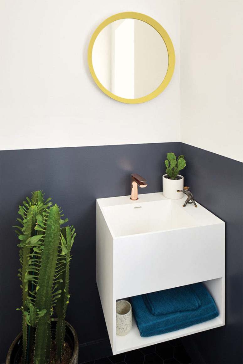 The powder room features color blocking, potted cacti and a floating sink with storage