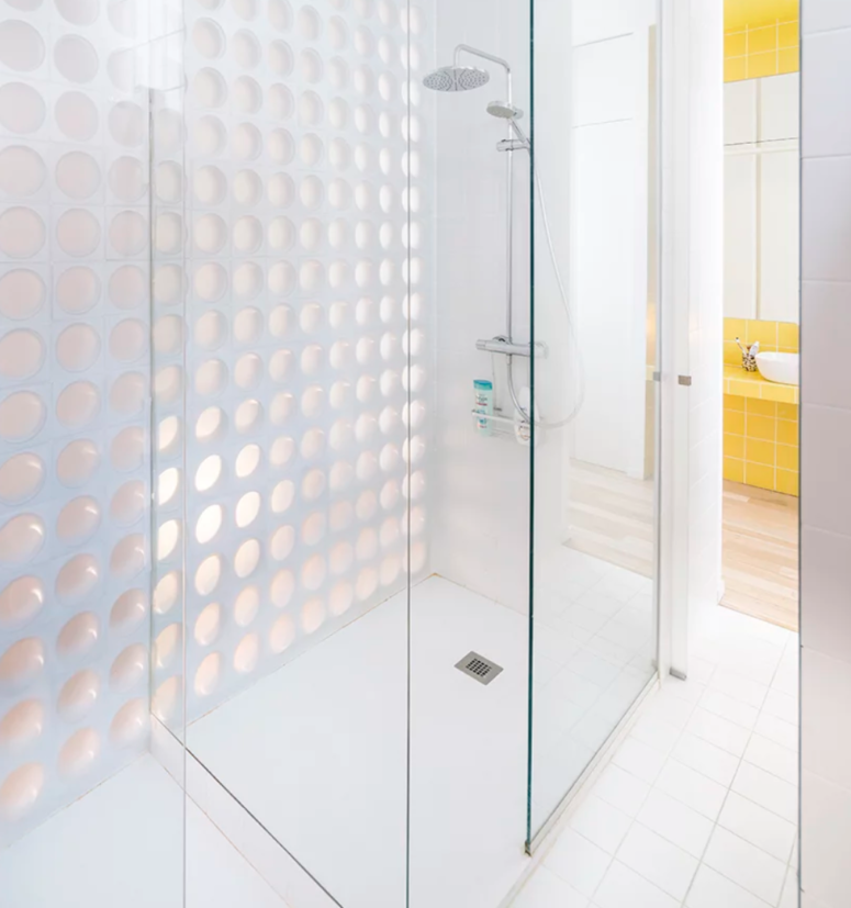 The shower space is all-white, with a perforated wall on one side