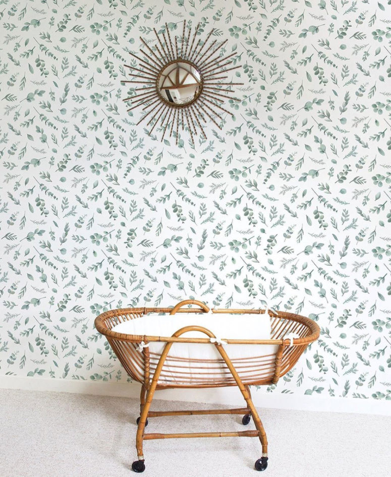 a boho nrusery with a leaf print accent wall that brings an outdoor feeling inside