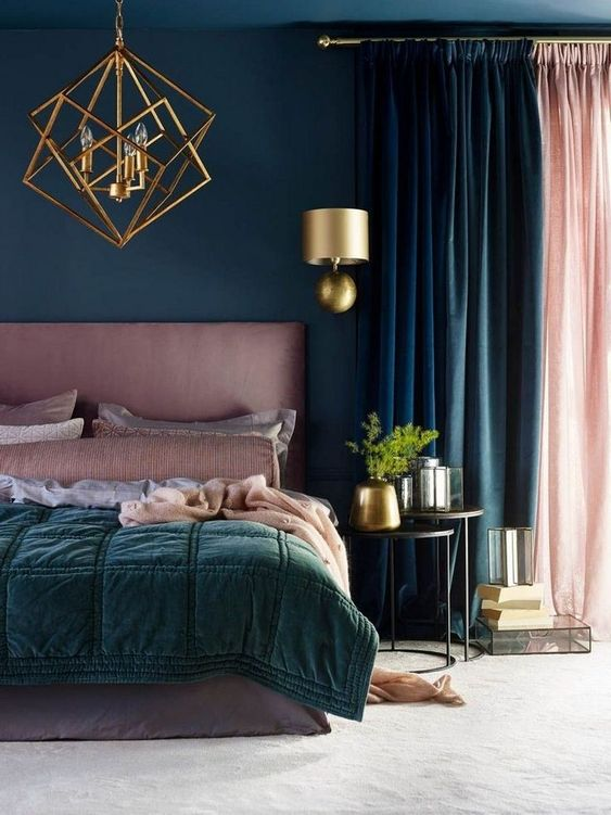 a bold bedroom done in teal, dark green and pink, with a gold planter, a wall sconce and a statement chandelier