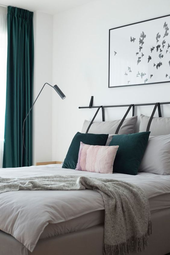 a bright contemporary bedroom done in white, grey and forest green, with grey hanging pillows as a headboard