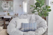 08 a dark wooden papasan chair with a neutral and pastel futon and pillows for a farmhouse space