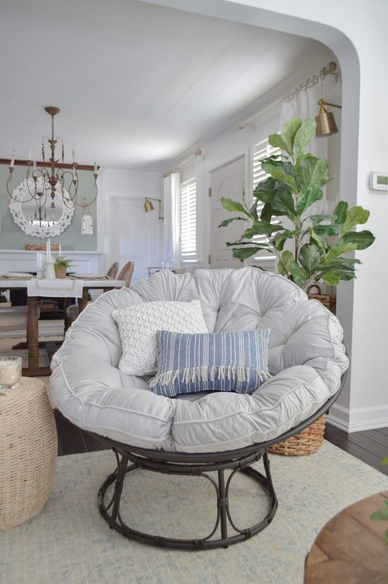 a dark wooden papasan chair with a neutral and pastel futon and pillows for a farmhouse space