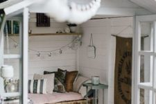 08 a small garden shed repurposed into a small bedroom with a pallet bed and pastel linens