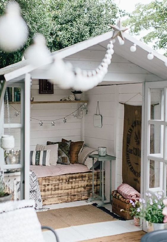 a small garden shed repurposed into a small bedroom with a pallet bed and pastel linens