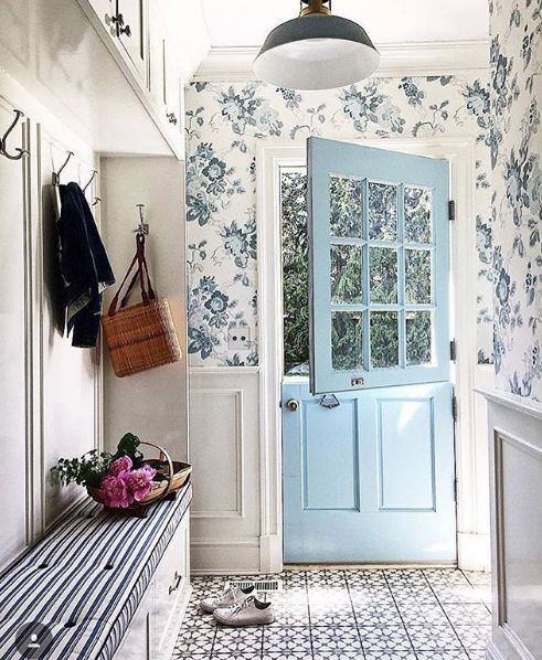 a vintage-inspired entryway with blue floral wallpaper and elegant wainscoting looks very chic and inviting