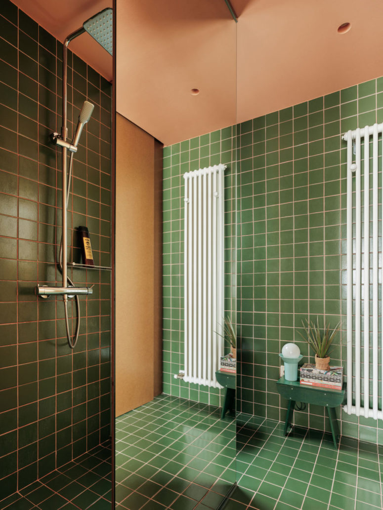 A floor to ceiling mirror separates the shower space from the rest of the bathroom