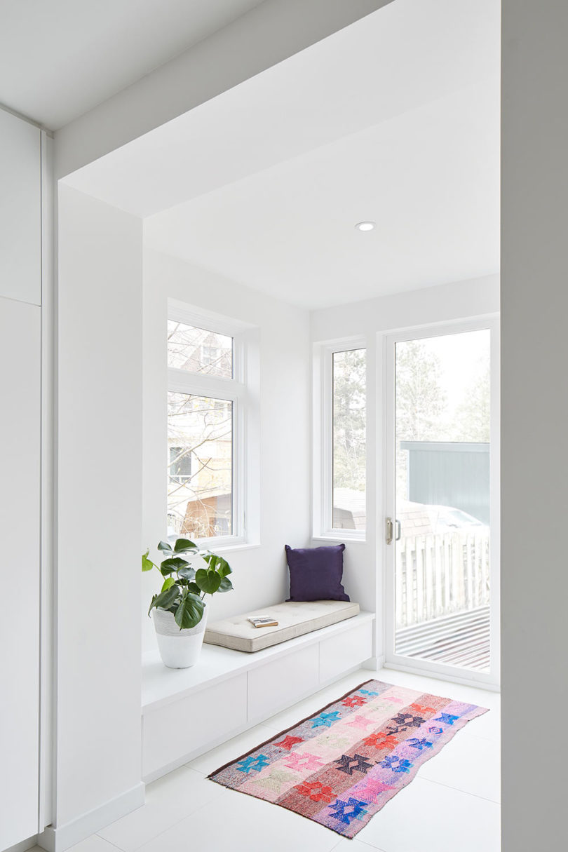 A small veranda with a reading nook, storage drawers is done with many windows to bring light in