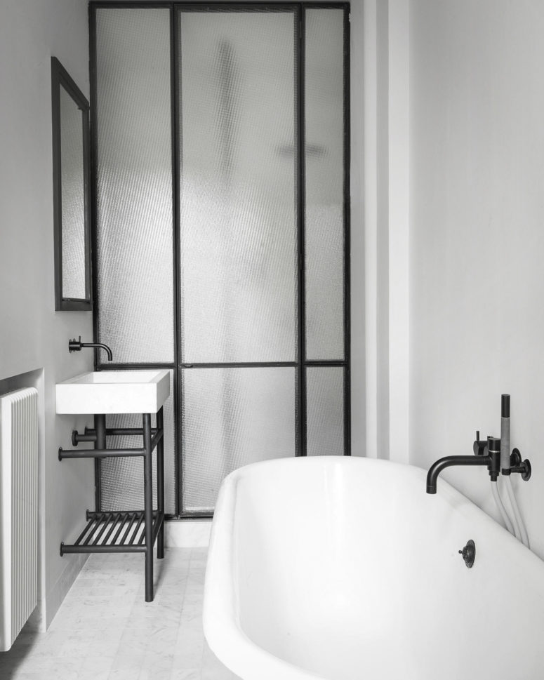 Another bathroom is done with white appliances, black fiixtures and the same black framed frosted glass