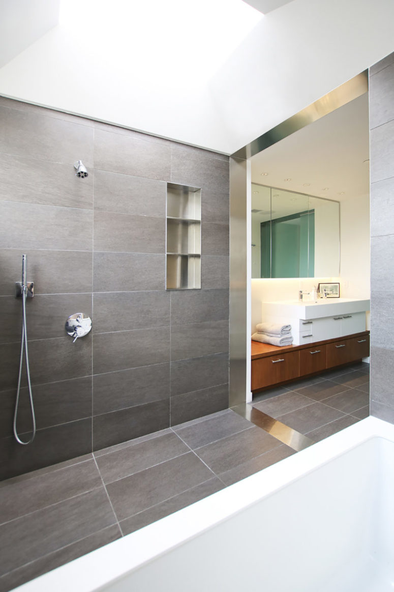 The bathroom is contemporary and clean, done with grey tiles and with clean tiles all over