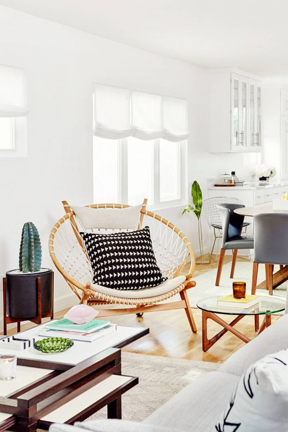 a papasan chair styled in a boho way, with macrame and monochromatic pillows for a boho space