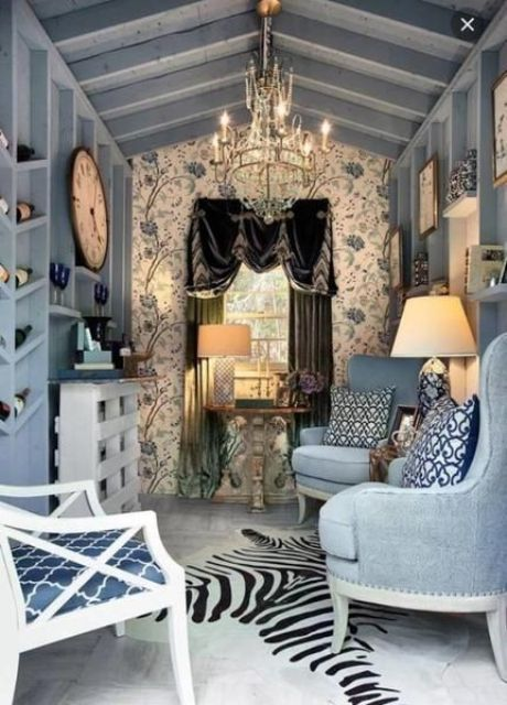 a refined she shed done in blues, with a gorgeous chandelier, a velvet curtain and some elegant accessories