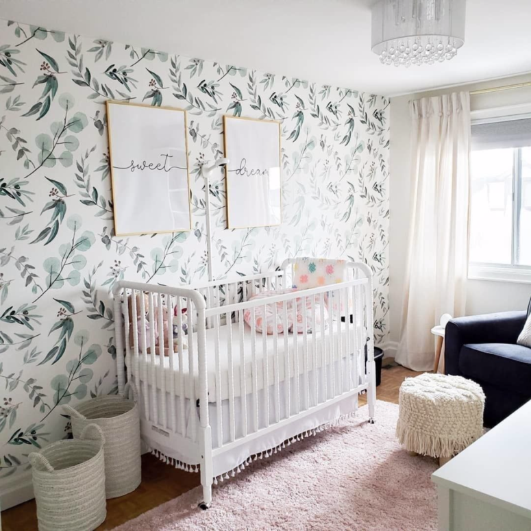 a welcoming and cool nurseyr in light shades and pastels plus a delicate leaf print accent wall